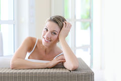 Beautiful woman sitting on a couch and resting Royalty Free Stock Image