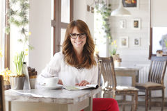 Beautiful woman sitting at desk in coffee shop Stock Image