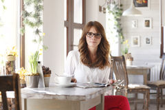 Beautiful woman sitting at desk in coffee shop Stock Photos