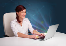 Beautiful woman sitting at desk and typing on laptop with abstract lights stock photos