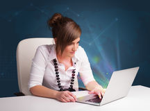 Beautiful woman sitting at desk and typing on laptop with abstract lights stock photo