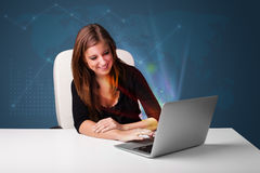Beautiful woman sitting at desk and typing on laptop with abstra Royalty Free Stock Photo
