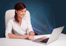 Beautiful woman sitting at desk and typing on laptop with abstra Stock Images