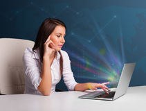 Beautiful woman sitting at desk and typing on laptop with abstra Royalty Free Stock Photography