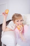 Beautiful woman sitting with a donut in his hand Stock Images