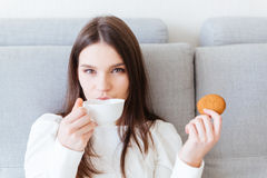 Beautiful woman sitting and drinking tea with cookie Stock Photography