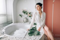 Beautiful woman sitting on the edge of the bath stock photos