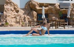 Beautiful woman sitting on the edge of swimming pool Royalty Free Stock Photo