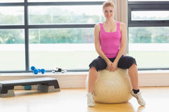Beautiful woman sitting on exercise ball in fitness studio Royalty Free Stock Image