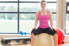 Beautiful woman sitting on exercise ball in fitness studio Stock Images