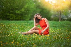Beautiful woman sitting on a field of dandelions Royalty Free Stock Photos