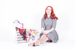 Beautiful woman sitting on the floor next to the bags with purchases Royalty Free Stock Image