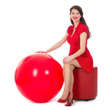 Beautiful woman sitting on footstool holding big red balloon Royalty Free Stock Photos