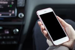 Beautiful woman while sitting on the front passenger seats in the car. Girl is using a smartphone. Hand closeup stock image