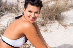 Beautiful woman sitting on golden beach sand Royalty Free Stock Photos