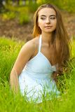 Beautiful woman sitting in the grass Royalty Free Stock Image