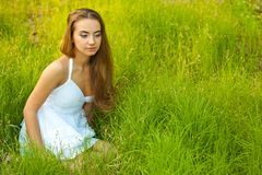 Beautiful woman sitting in the grass Royalty Free Stock Images