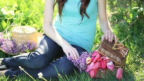 Beautiful woman sitting on the grass with basket of flowers