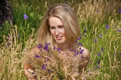 Beautiful woman sitting in grass with a flowers Royalty Free Stock Photography