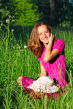 Beautiful woman sitting in grass and laughs Royalty Free Stock Image