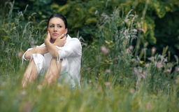 Beautiful woman sitting in a grass. Royalty Free Stock Images