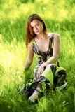 Woman sitting in a green field Stock Images