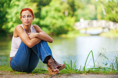 Beautiful woman sitting on ground. Carroty beautiful woman sitting on ground and dreams, on green park summer Stock Image