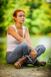 Beautiful woman sitting on ground. Carroty beautiful woman sitting on ground and dreams, on green park summer Stock Photo