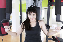 Beautiful woman sitting on the gym equipment royalty free stock images
