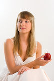 Beautiful woman is sitting and holding red apple Stock Photography