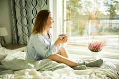 Beautiful woman sitting at home on a bed by big window with cup of hot coffee. Wearing shirt. Cozy sunny bedroom filled with light. beautiful morning behind the stock photo