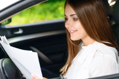 Beautiful woman sitting inside car and reading Stock Image