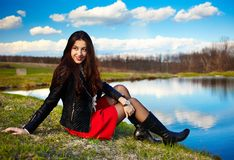 Beautiful woman sitting on a lake's shore Royalty Free Stock Image