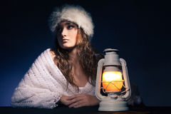 Beautiful woman sitting with lantern over dark Stock Image