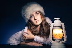 Beautiful woman sitting with lantern over dark Stock Image