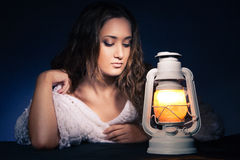 Beautiful woman sitting with lantern over dark Stock Photo