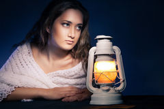 Beautiful woman sitting with lantern over dark Royalty Free Stock Photos