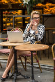 Beautiful woman sitting with a laptop at outdoor cafe talking on cell phone. Stock Photo