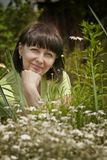 Beautiful woman. Sitting on the lawn, where the flowers grow Royalty Free Stock Images