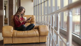 Beautiful woman sitting on leather armchair with tablet computer. stock video
