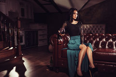 Beautiful woman sitting on a leather vintage sofa Royalty Free Stock Photos