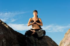 Beautiful woman sitting in lotus pose on the beach Royalty Free Stock Photo