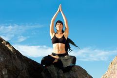 Beautiful woman sitting in lotus pose on the beach Stock Photography