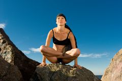Beautiful woman sitting in lotus pose on the beach Stock Photo