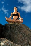Beautiful woman sitting in lotus pose on the beach Royalty Free Stock Photography