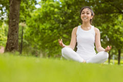 Beautiful woman sitting in lotus pose at park Royalty Free Stock Photo