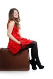 A beautiful woman is sitting on a luggage Royalty Free Stock Photography