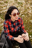 Beautiful woman sitting in the middle of a flowery meadow. Beautiful woman with sunglasses sitting in the middle of a flowery meadow stock image