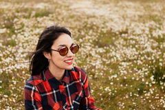 Beautiful woman sitting in the middle of a flowery meadow. Beautiful woman with sunglasses sitting in the middle of a flowery meadow royalty free stock image