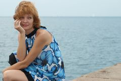 Beautiful woman sitting on the mooring Royalty Free Stock Photography